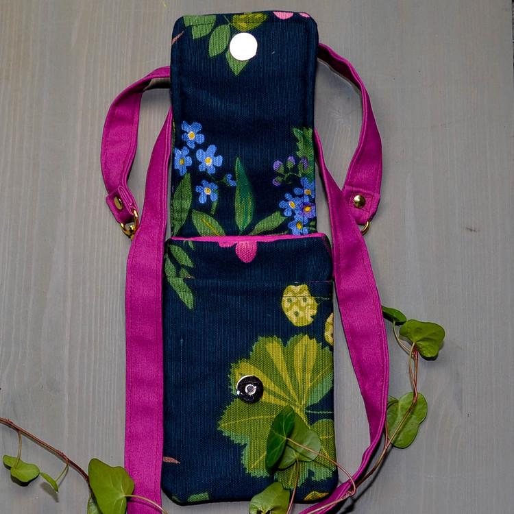 Mobilväska liten med öppet lock mörkblå botten, gröna blad och ljusblå små blommor. Bärrem i cerise.
