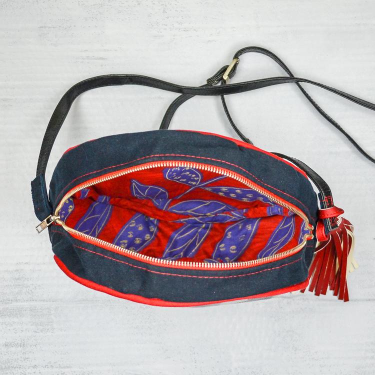 Stående rund väska öppen med foder i rött och blått, rött blixtlås. Röd lång lädertofs i sidan. Lång svart läderrem
