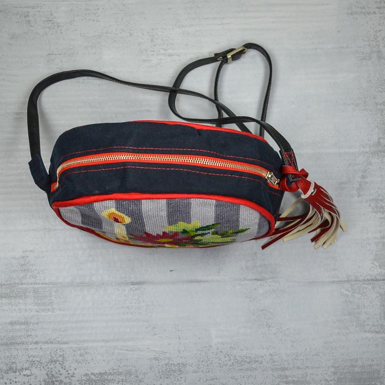 Stående rund väska med svart kant, rött blixtlås. Framsida korsstygnsbroderi. Röd lång lädertofs i sidan. Lång svart läderrem