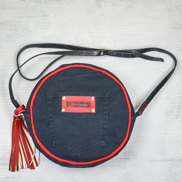 Svart rund väska med jeansficka företagsmärkt AnnaDacap i rött. Svart lång läderrem