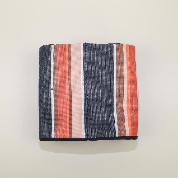 Liggande väskorganiserare  i orange och grått mönster hoprullad