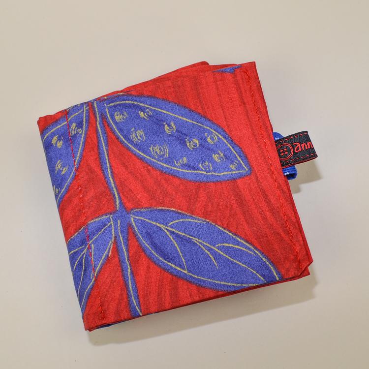 Liggande väskorganiserare  i rött och blått mönster hoprullad