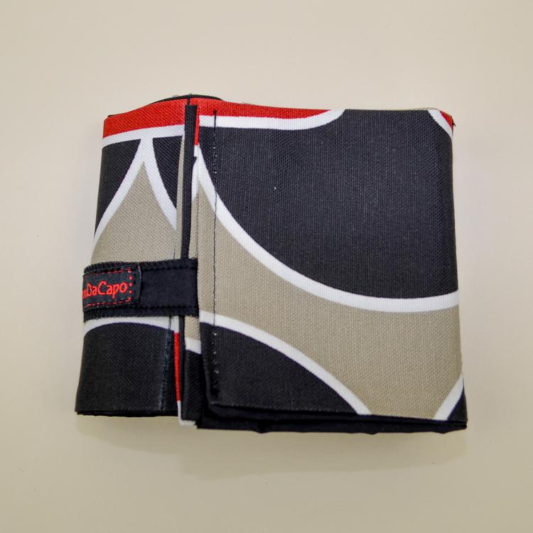 Liggande väskorganiserare rött, svart och grått mönster hoprullad