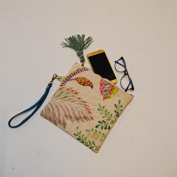 Handledsväska Clutch Tofs framsida med glasögon och mobil