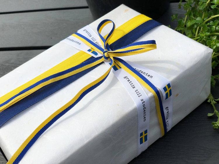 Ett paket inslaget med sverigebandet istället för snöre.