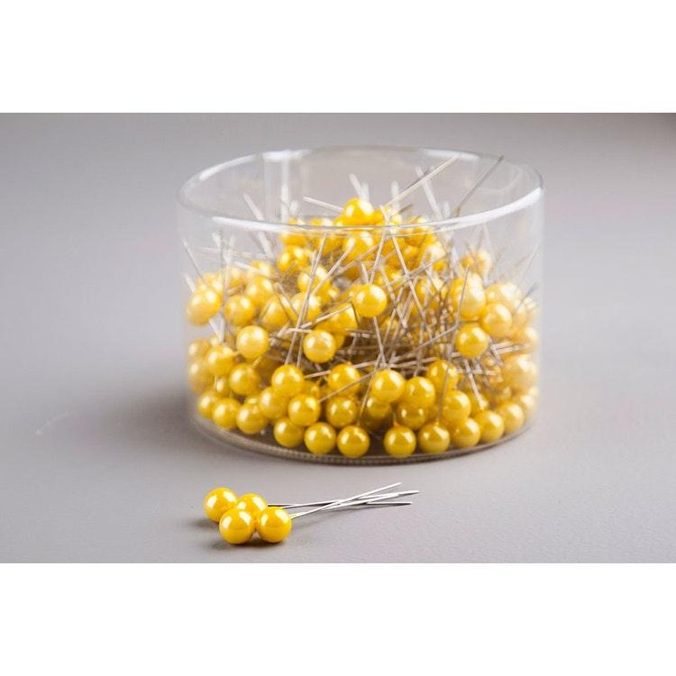 En ask med gula pärlnålar