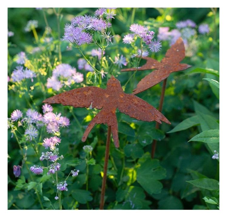 Närbild på två svalor bland blommor