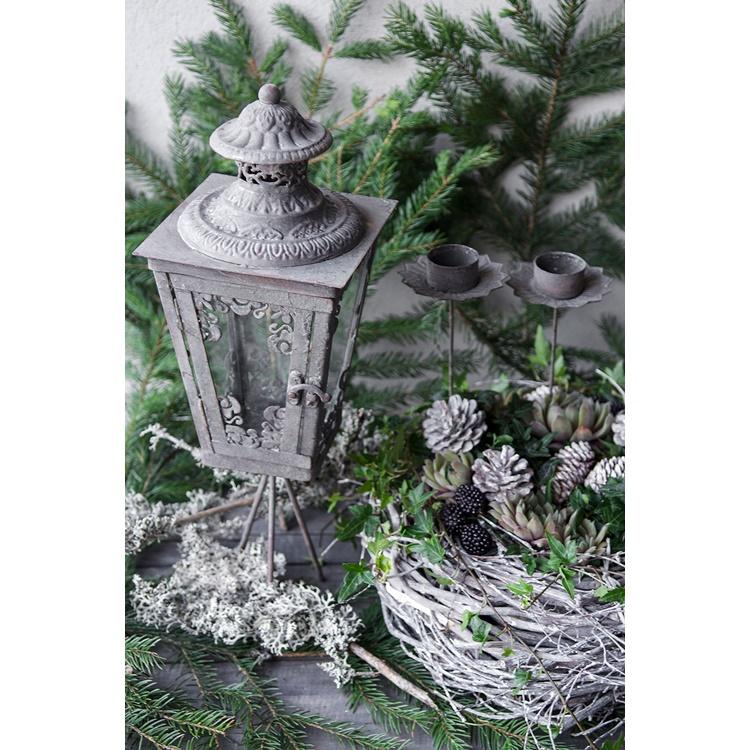 Lykta med ornament på en trefot.