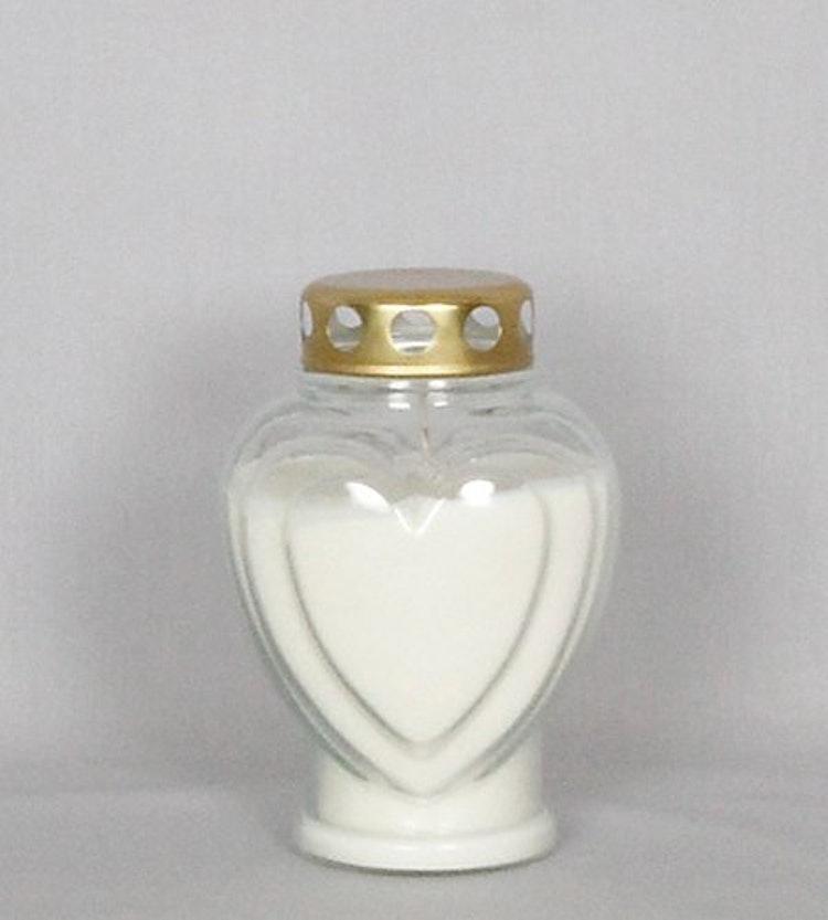 Ett oljeljus i hjärtformat glas med guldlock