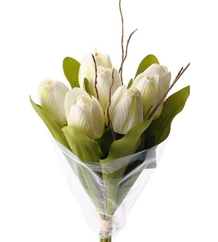 En bukett med sju vita konstgjorda tulpaner och några kvistar.