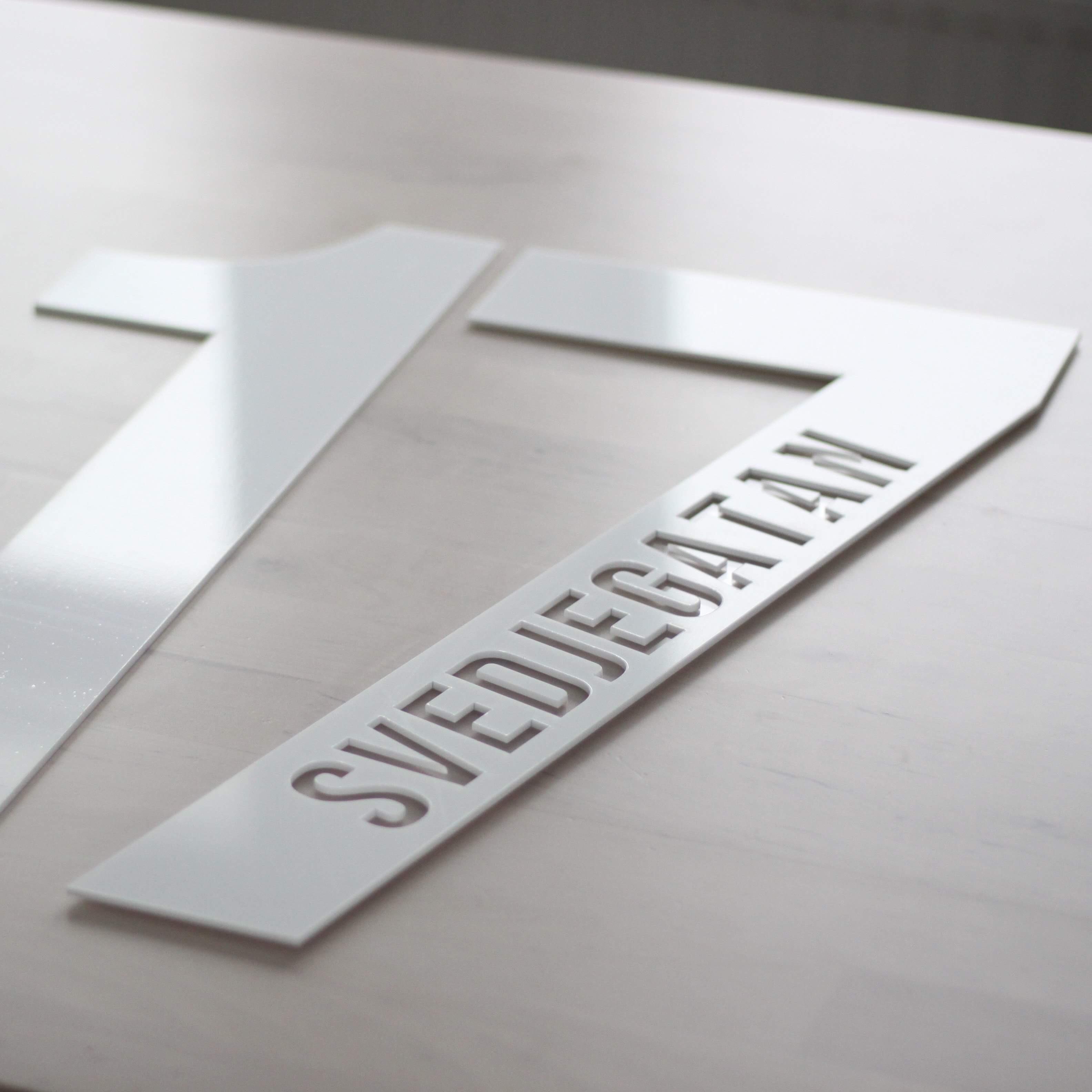 Fasadsiffra med text DESIGN BY S.H