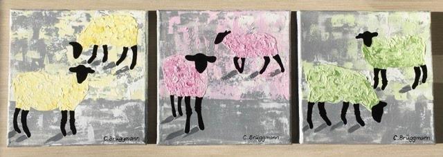 Tre tavlor med får i pastellfärger målade av svenska konstnären C.Brüggmann. Gotlandsfår, fårsaker och Visby står för inspirationen.