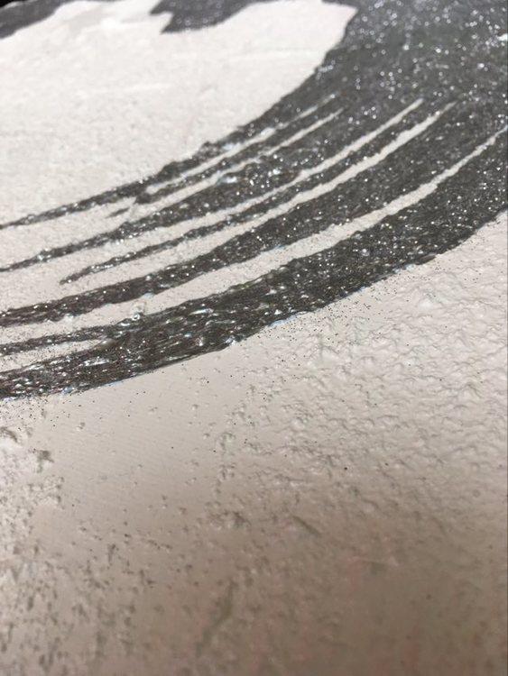 Detaljstudie på hjärttavla i silver, vitt och svart med glitter på. Stilren svensk konst.
