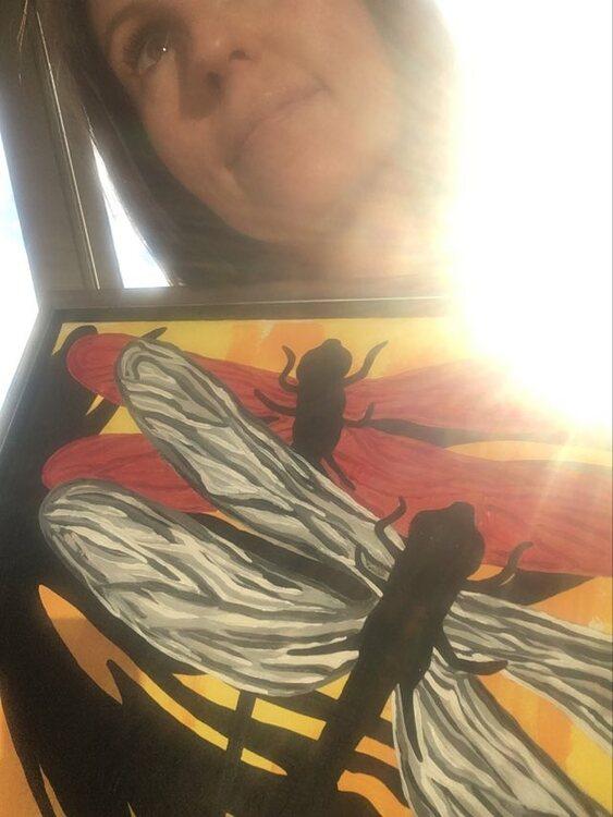 Stolt konstnär med sin färgglada tavla. Tavla med rött, grått, gult och orange.