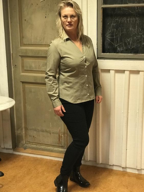 Skjortan Lina mossgrön i 100% GOTS bomull. Söta metallknappar. Bild framifrån på modell i storlek 40.