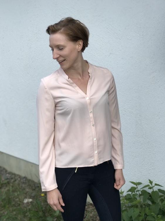 Blusen Isabelle gammelrosa i Oeko-Tex märkt polyester. Med vacker farfarskrage och pärlemorknappar. Bild på modell i storlek 36.