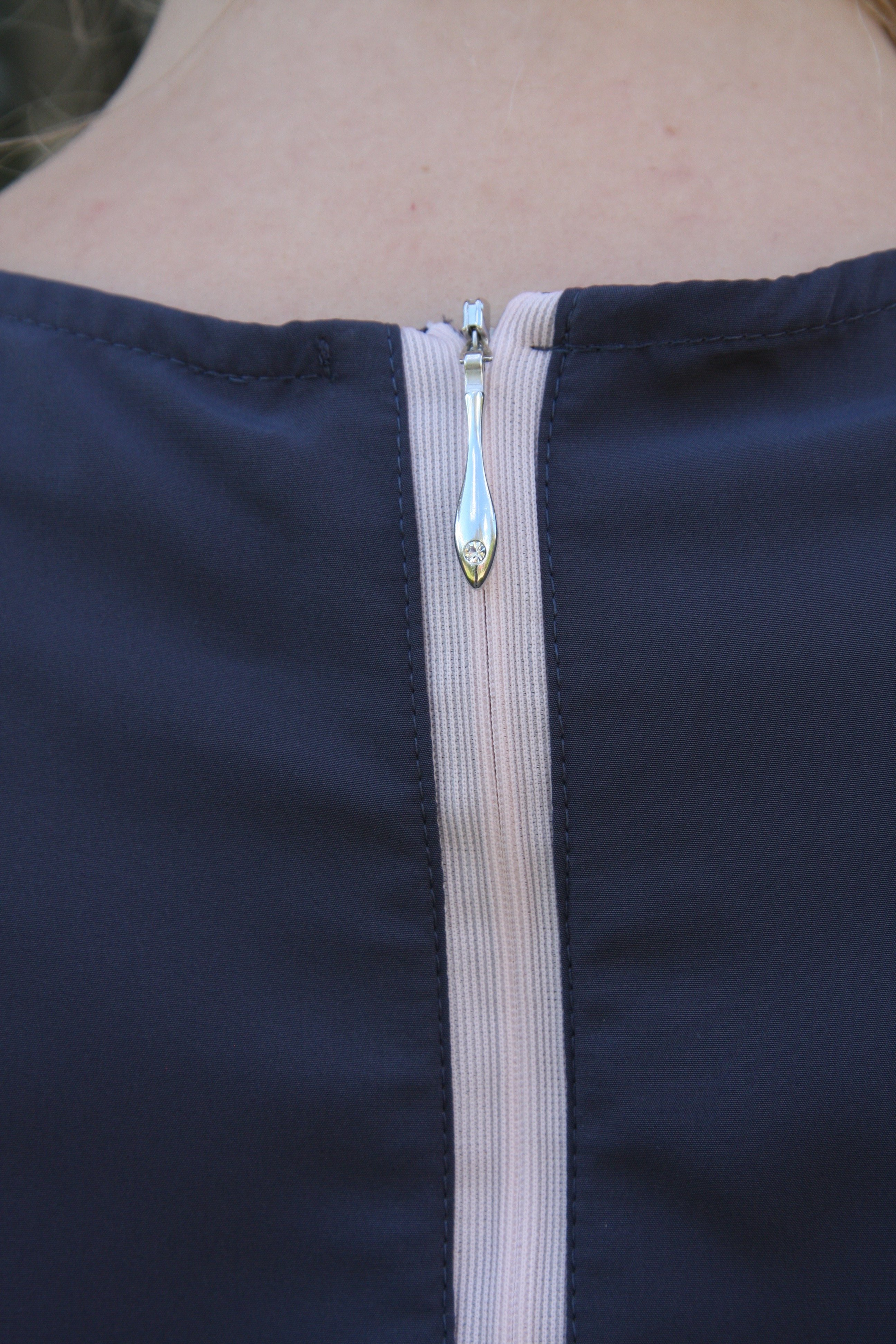 Alexandra blågrå med rosa dragkedja i nacken med fin hängare. Närbild på dragkedja.