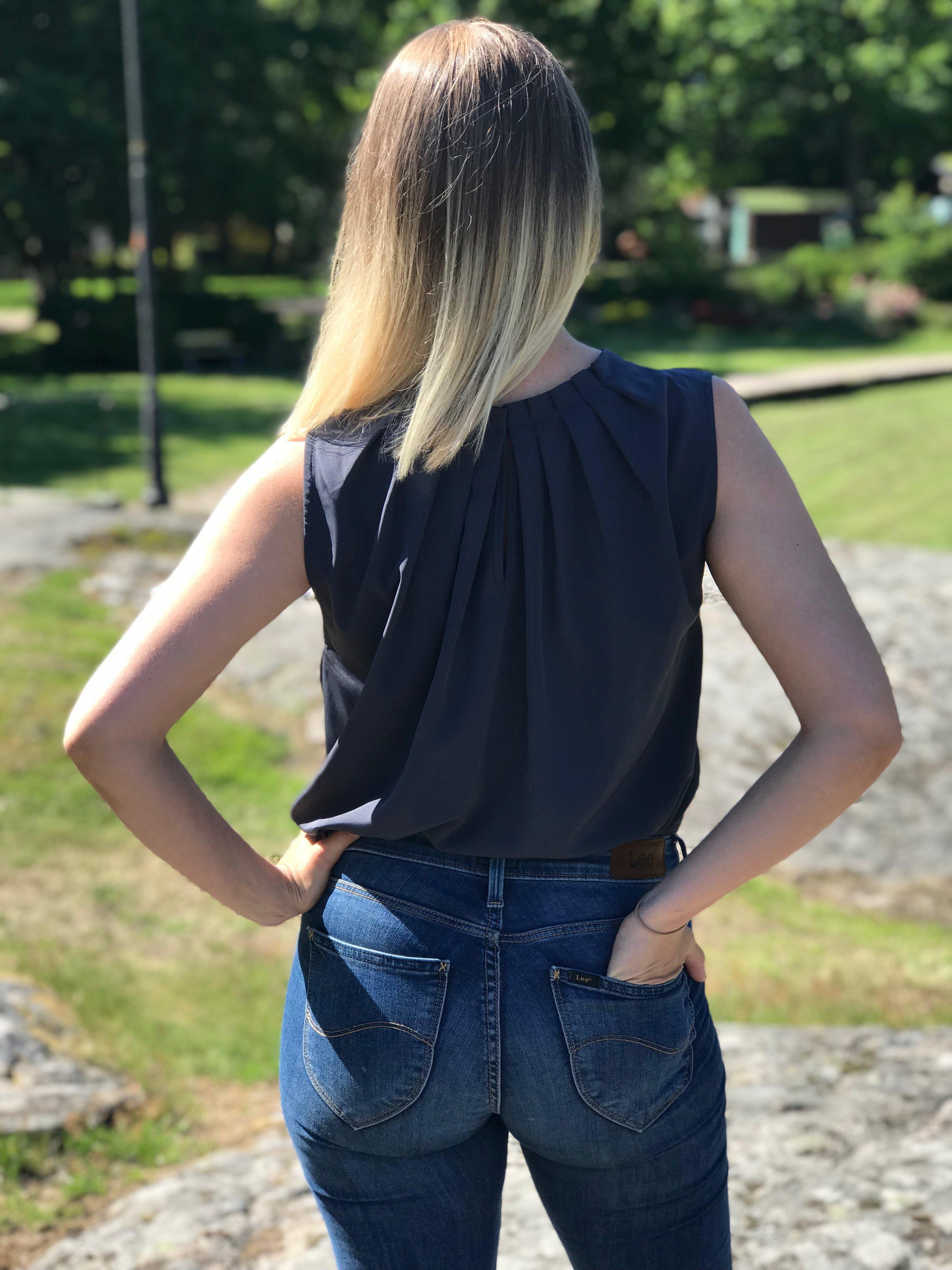 Blus/topp Pauline gråblå med vacker plisserad krage. Bild bakifrån på toppen instoppad i byxor, storlek 36.