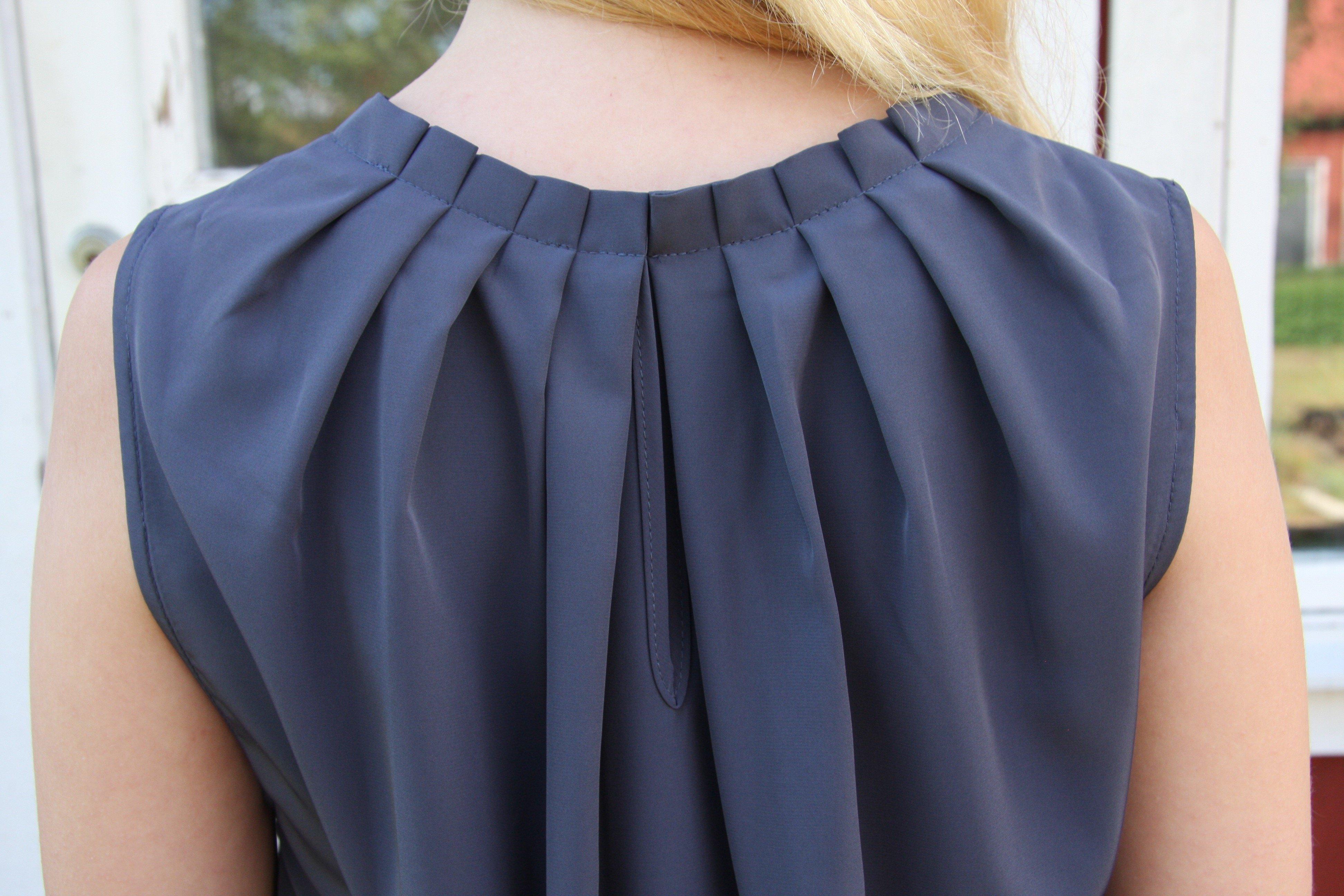 Blus/topp Pauline gråblå med vacker plisserad krage. Bild på krage bakifrån.