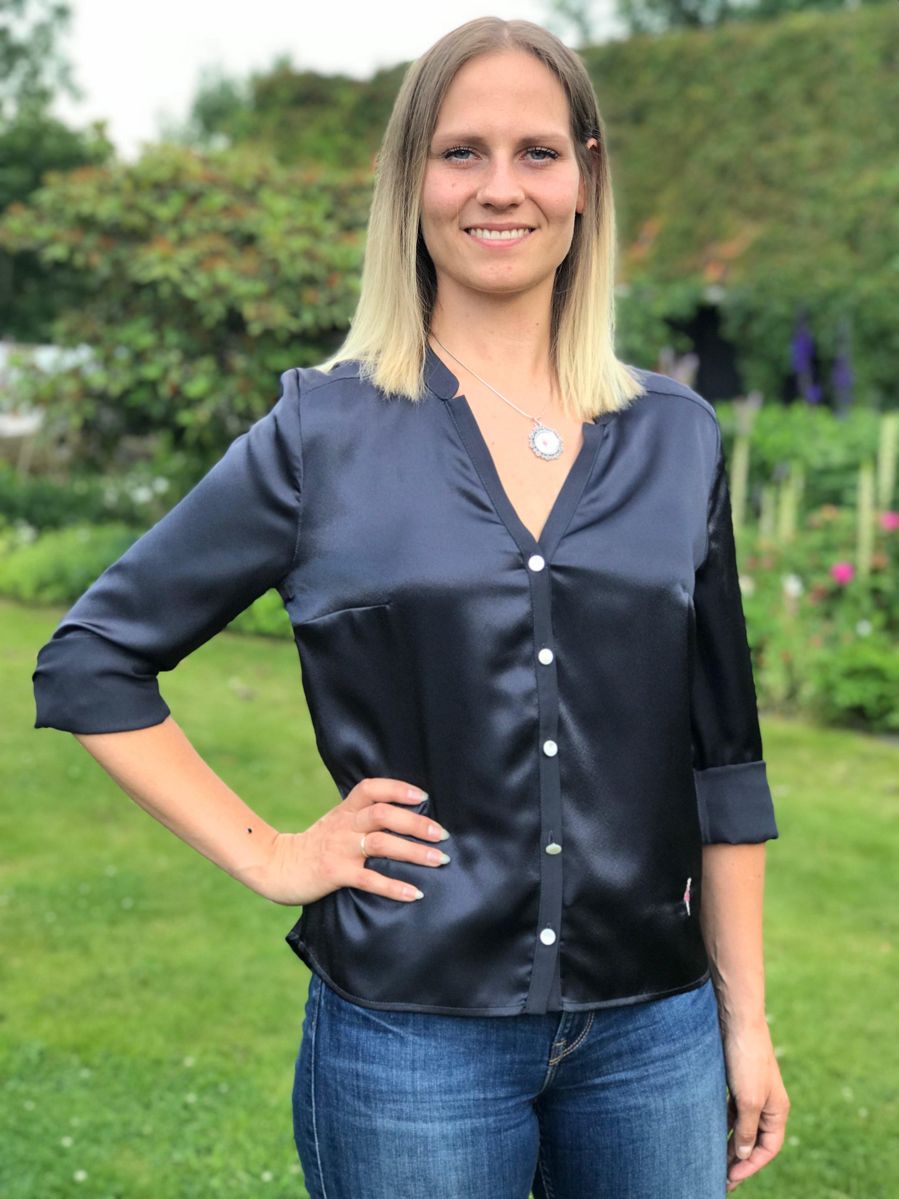 Blusen Isabelle blågrå i Oeko-Tex märkt polyester. Med fina pärlemorknappar. Bild framifrån med upprullade ärmar i storlek 36.