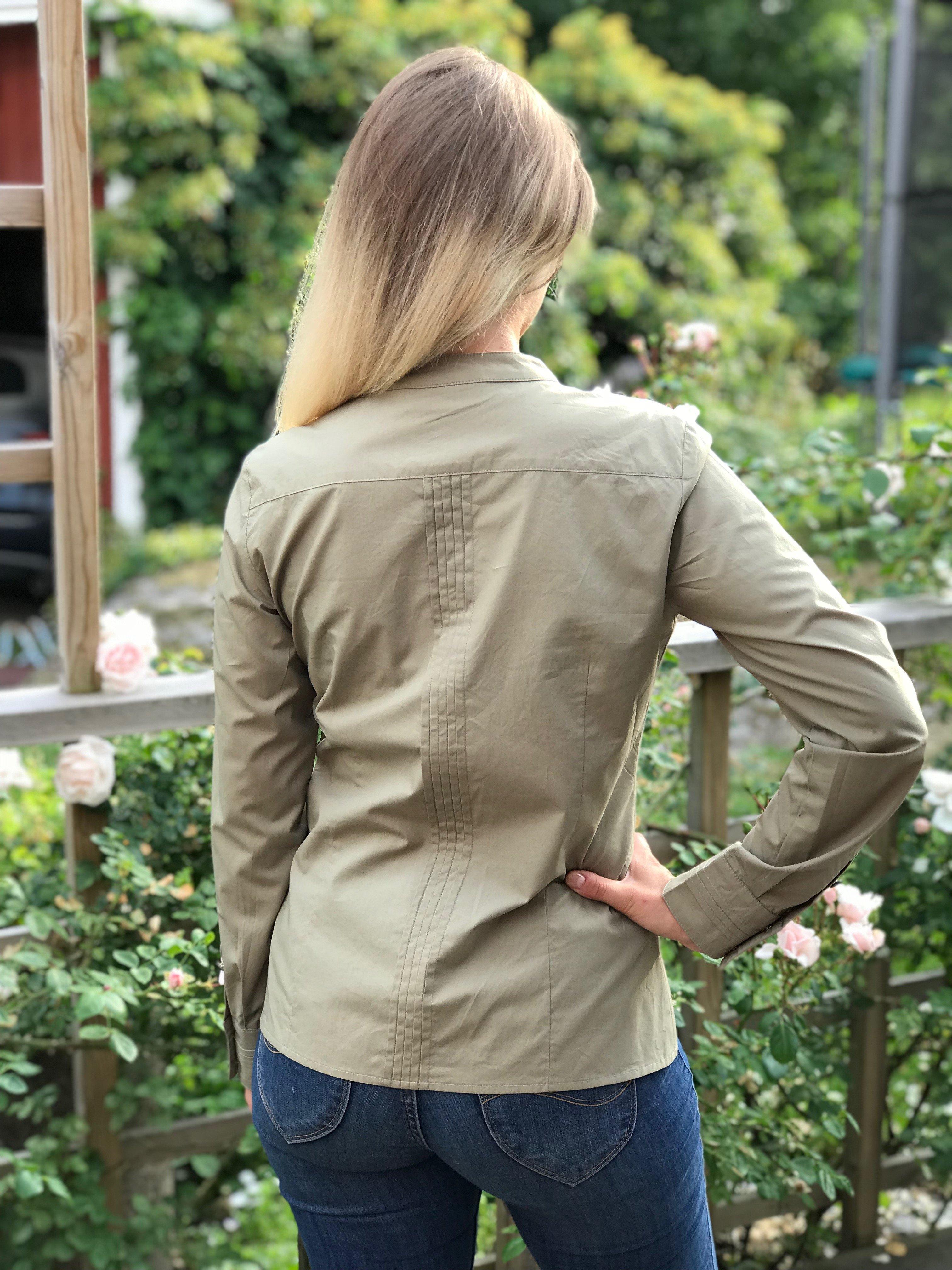 Skjortan Lotta mossgrön i 100% GOTS bomull med pärlemorknappar. Bild bakifrån i storlek 36.