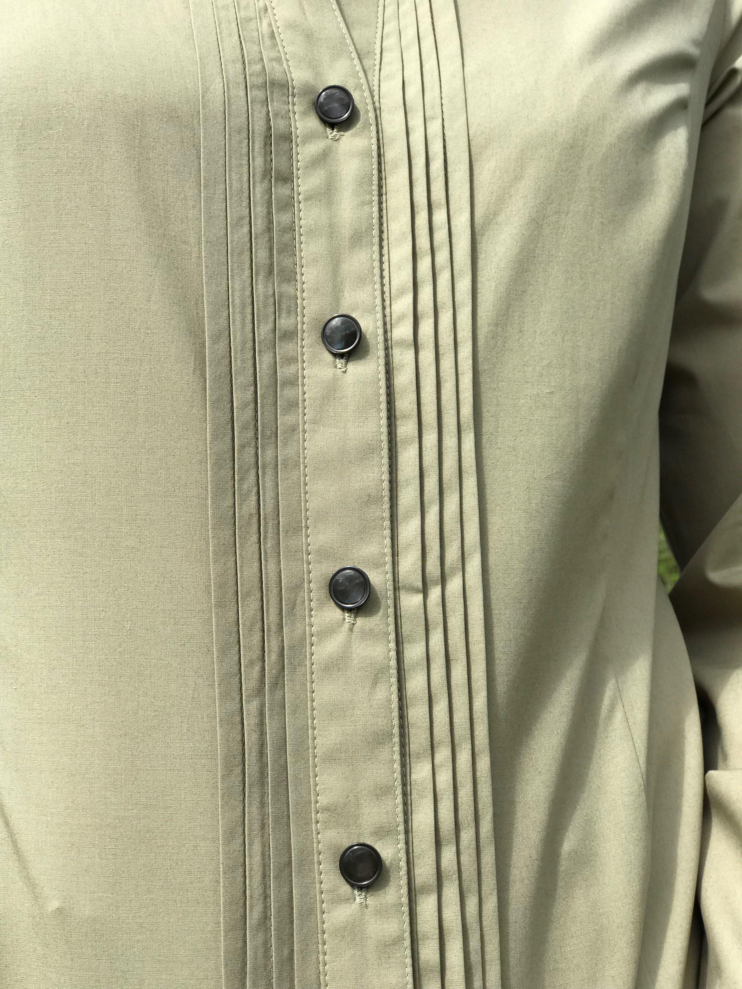 Skjortan Lotta mossgrön i 100% GOTS bomull med pärlemorknappar. Bild på knäppning fram.