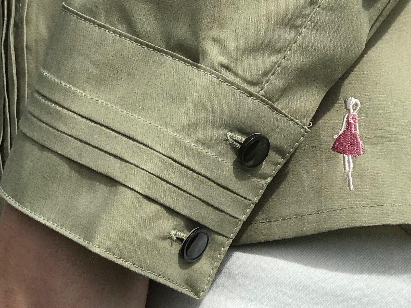 Skjortan Lotta mossgrön i 100% GOTS bomull med pärlemorknappar. Bild på manschett och Keep the Fashions broderade logga.