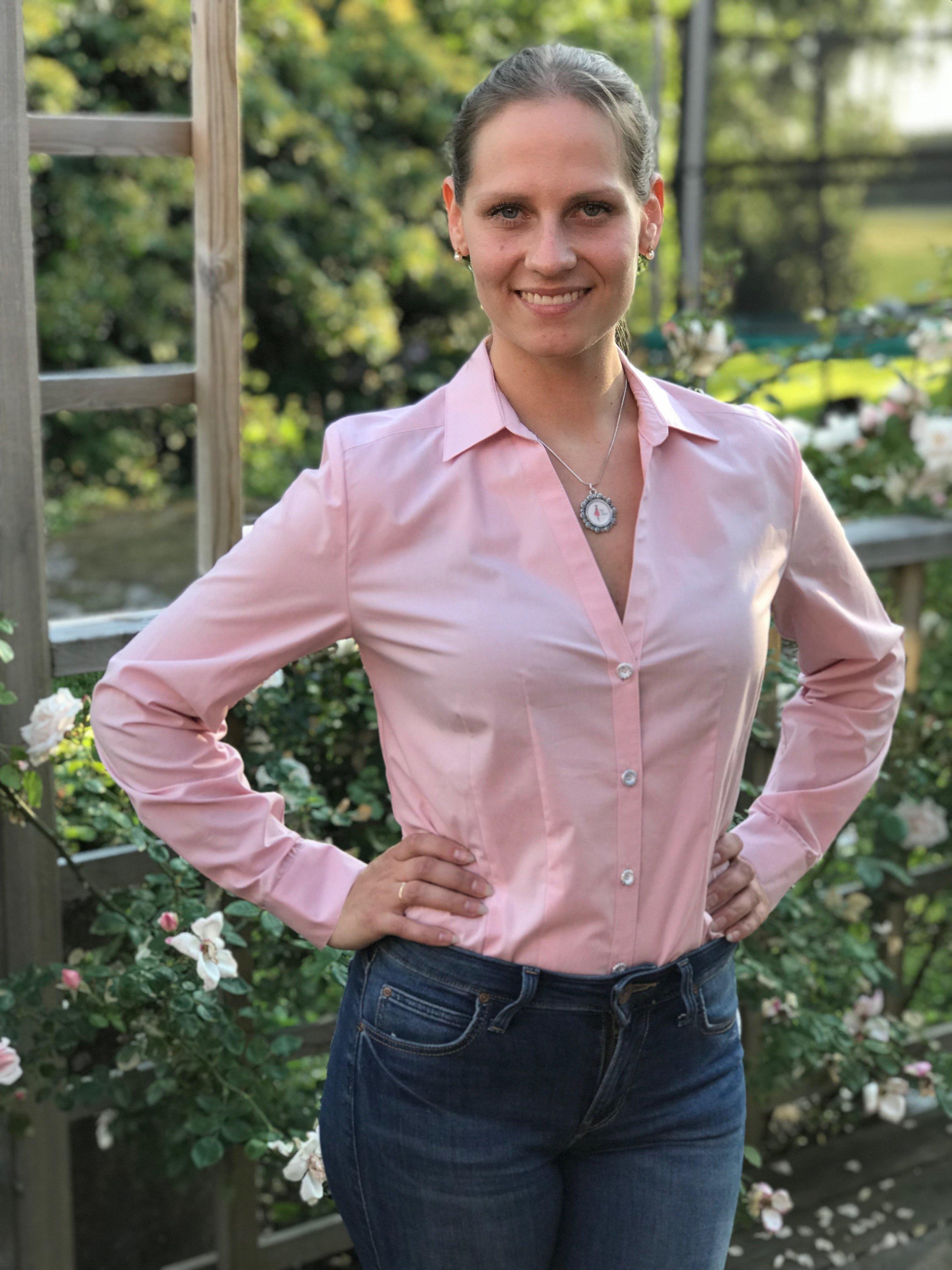 Skjortan Lina rosa i 100% GOTS bomull. Söta metallknappar. Bild framifrån med skjortan istoppad i byxor. Storlek 36.