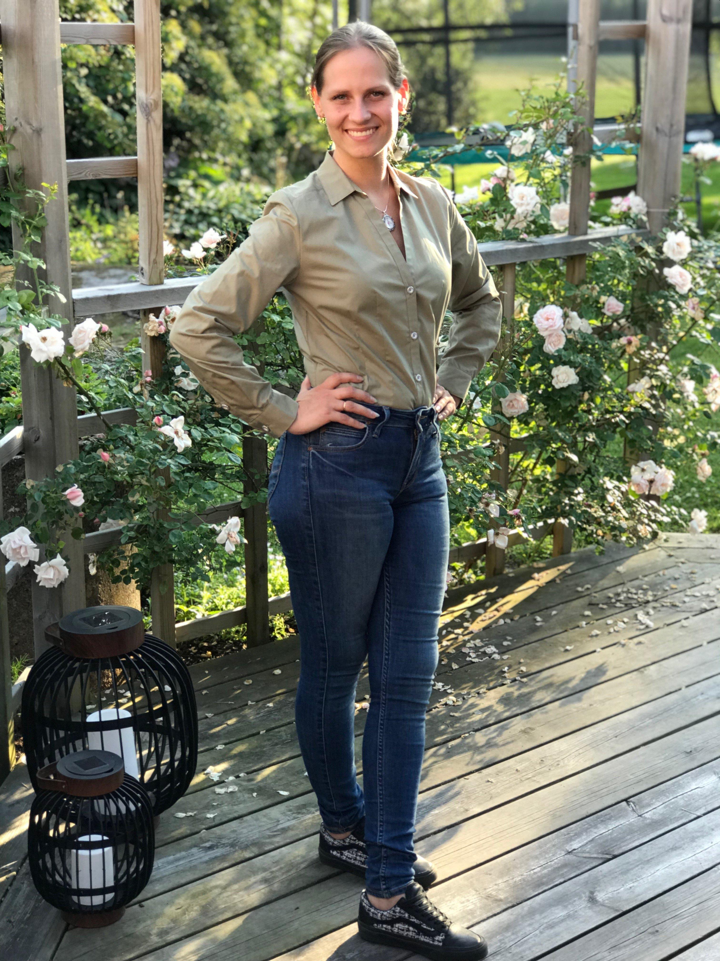 Skjortan Lina mossgrön i 100% GOTS bomull. Söta metallknappar. Bild från sidan med skjortan instoppad i byxor. Storlek 36.