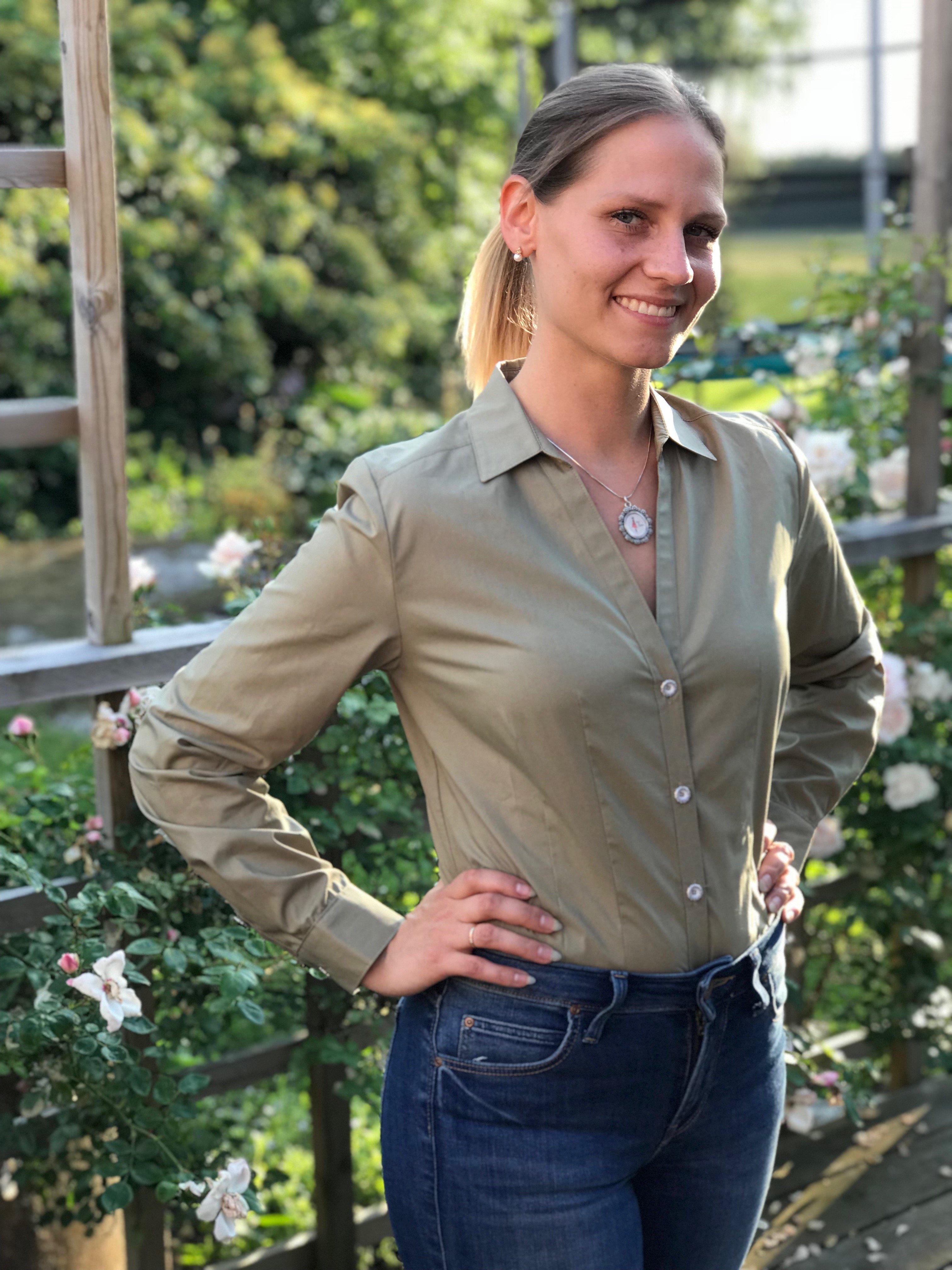 Skjortan Lina mossgrön i 100% GOTS bomull. Söta metallknappar. Bild framifrån med skjortan instoppad i byxor. Storlek 36.