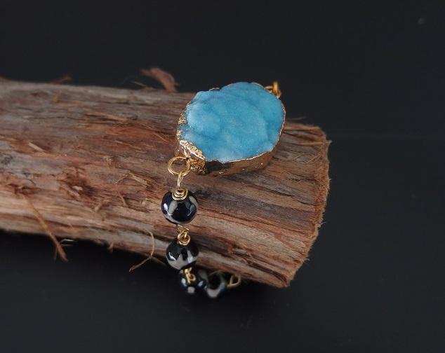 Blått druzy agat armband med svarta stenar.