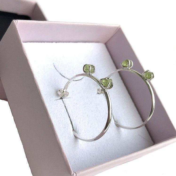 Silverörhängen runda ringar med peridot stenar.