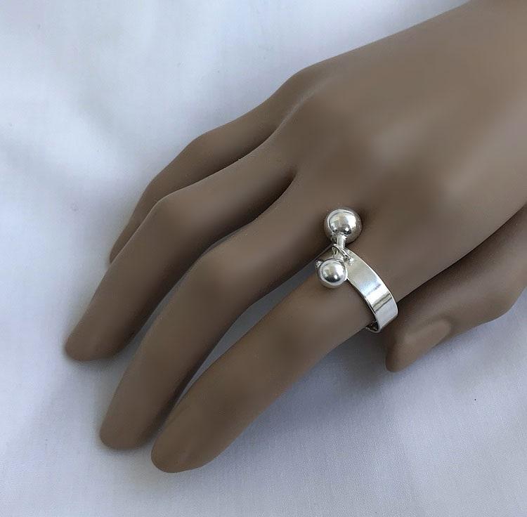 Slät bred silverring med rörlig pinne och kulor på