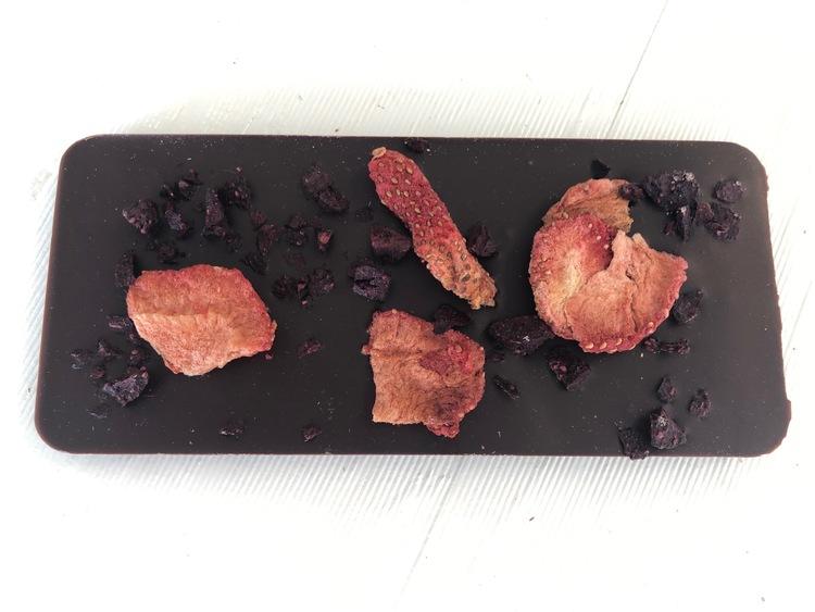 Chokladkaka av mörk choklad toppad med frystorkade jordgubbar & blåbär
