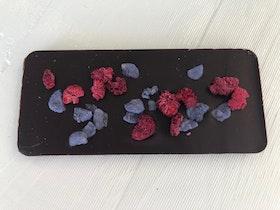 Chokladkaka av mörk choklad toppad med kanderade violer & frystorkade hallon.