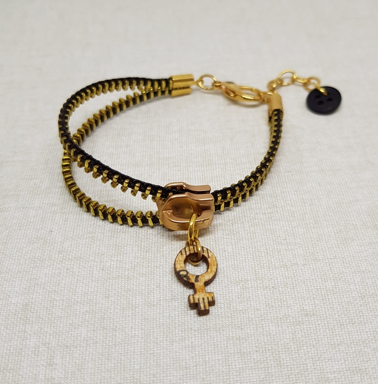 Armband blixtlås  - svart/guld med feministsymbol