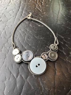 Halsband av återvunna knappar och blixtlås -grått