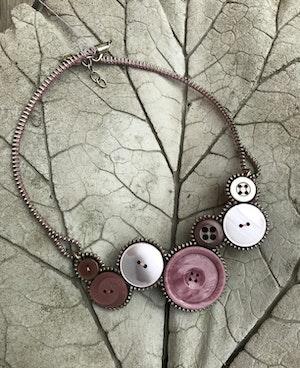 Halsband av återvunna knappar och blixtlås - rosaskimmer