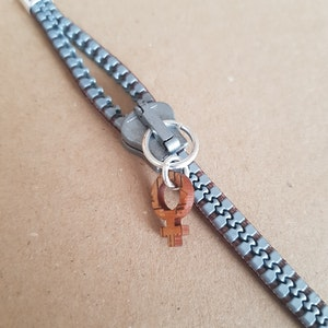 Armband blixtlås  - silvrigt/brunt med feministsymbol