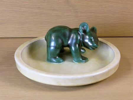 Green bear standing on dish