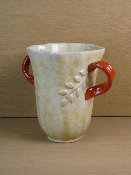 large yellowish vase with orange handles