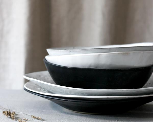 Stort keramikfat och stora keramiksskålar i grålera, vit och svart