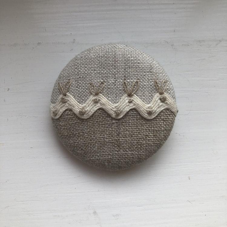 Handgjord brosch i linnetyger  och band   5 cm i diameter.