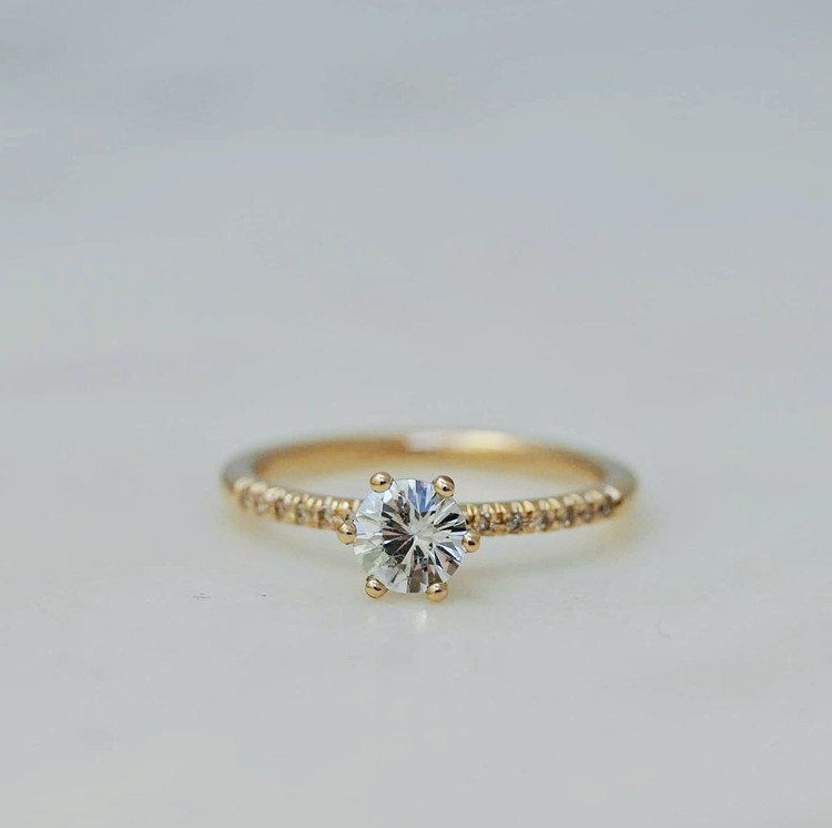 """Andromeda"" in gold with a white sapphire and small diamonds"