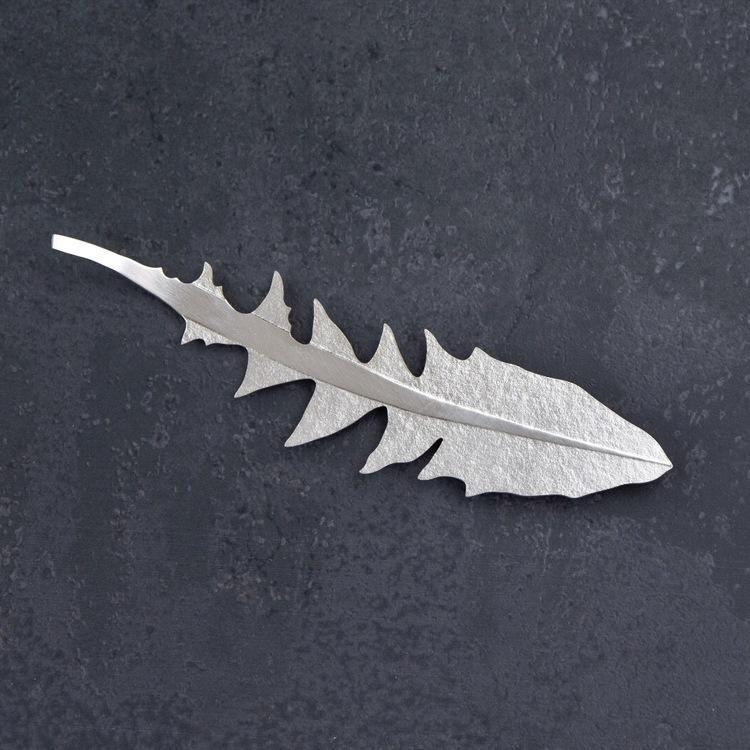 Brosch i form av ett maskrosblad. Tillverkad för hand av silver, broschnålen är gjord av nysilver.