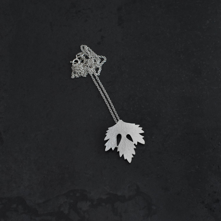Ett litet persiljeblad som hänge på en kedja. Persiljebladet är ca 2,5 X 2,7 cm och har en lite matt struktur på ytan. Kedjans längd är 42 cm.