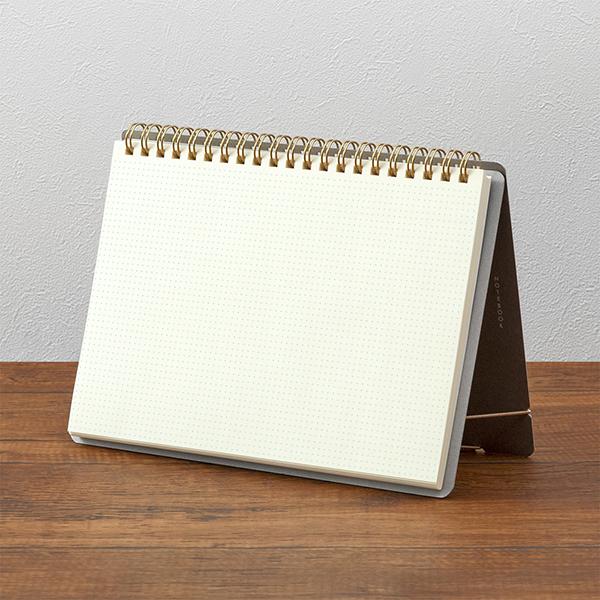 Midori + Stand Notebook [A5] Cross Grid uppställd på ett bord