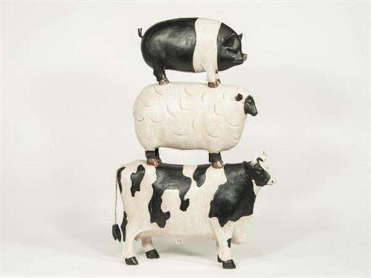 Ko, lamm och gris i höjd. Står på varandras ryggar.