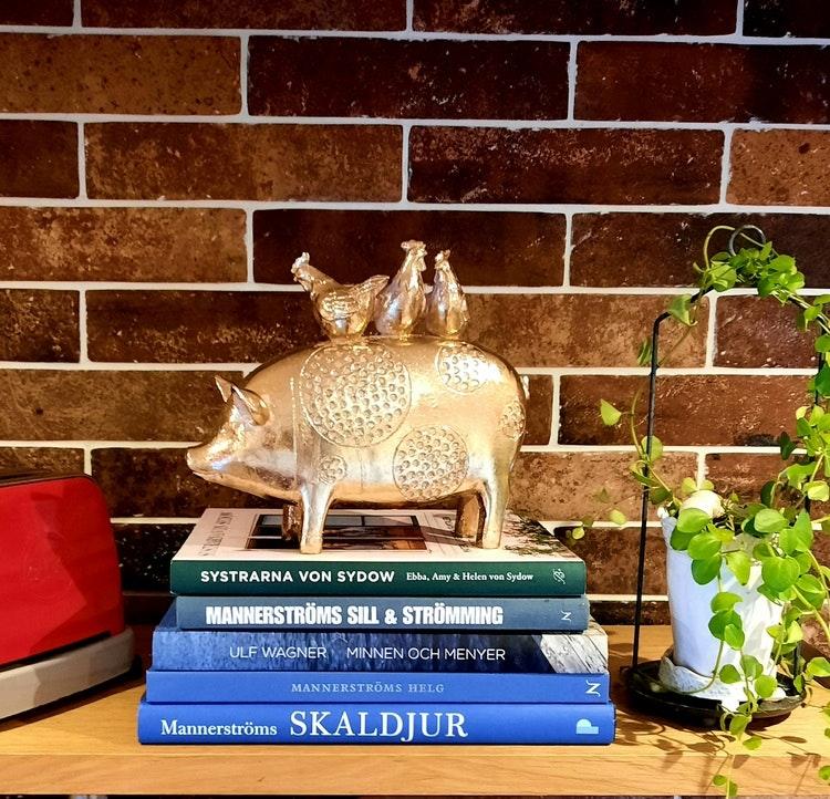 Snygg guldig dekoration med gris och hönor.