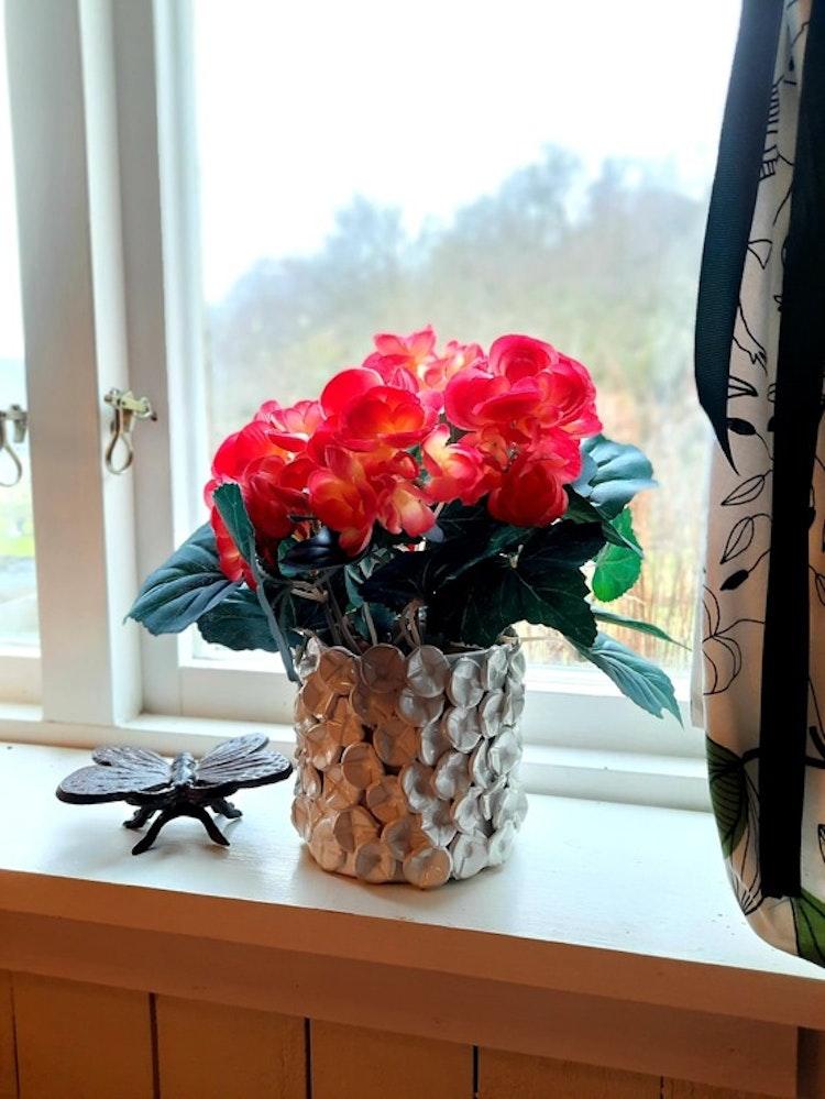 Blomkruka med blommor i kökets fönster.